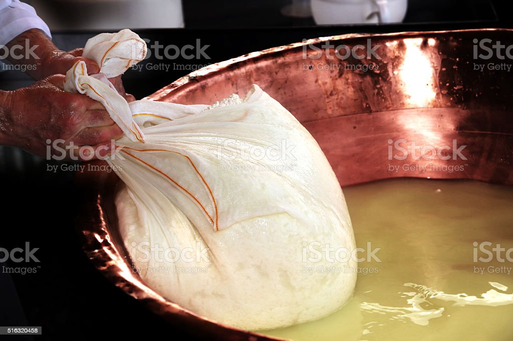 Senior cheesemaker collects the cheese stock photo