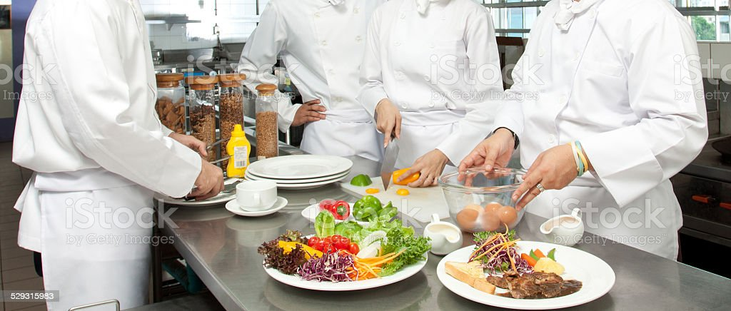 senior chef giving cooking lesson to young chefs stock photo