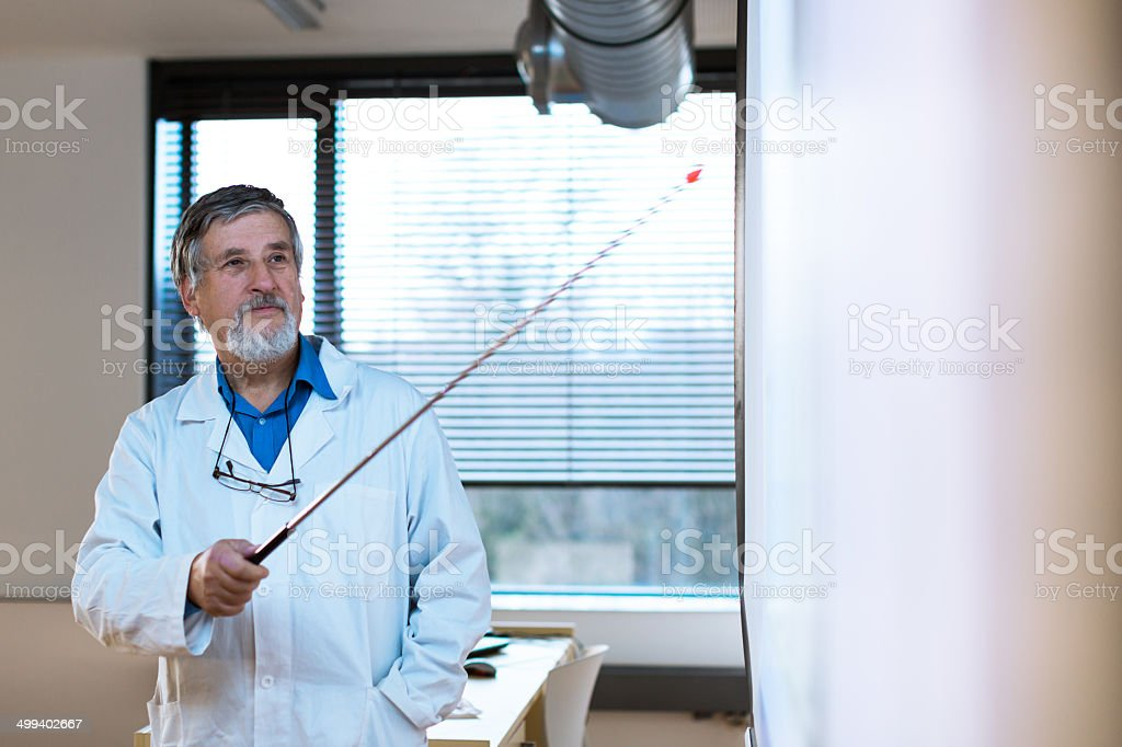 Senior chemistry professor giving a lecture in front of classroo royalty-free stock photo