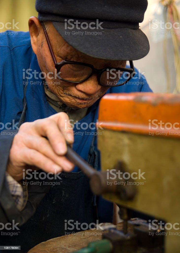Senior Chinese Man Cutting Keys stock photo