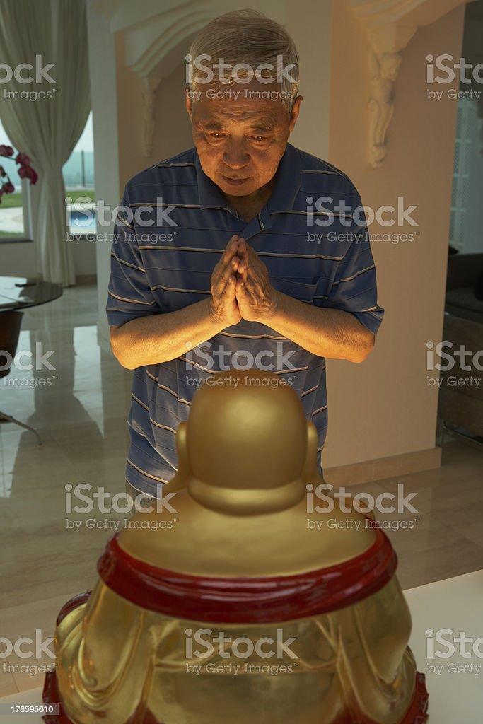 Senior Chinese Man Praying To Statue Of Buddha At Home royalty-free stock photo