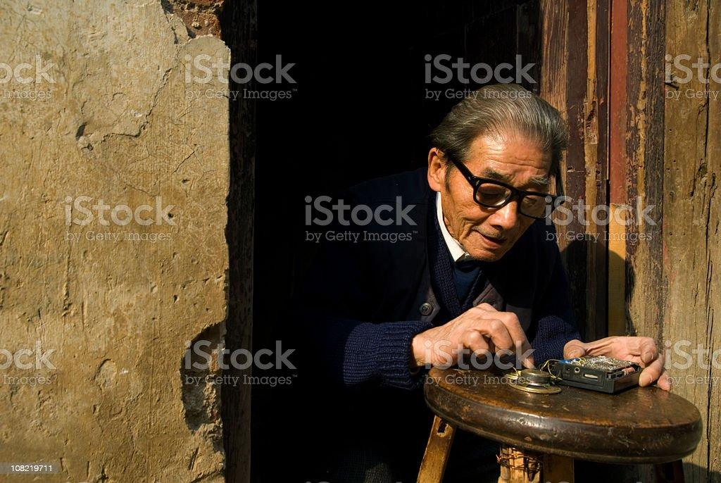 Senior Chinese Man Repairing Radio in Doorway stock photo