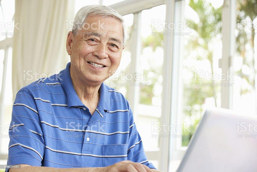 Senior Chinese Man Sitting At Desk Using Laptop stock photo