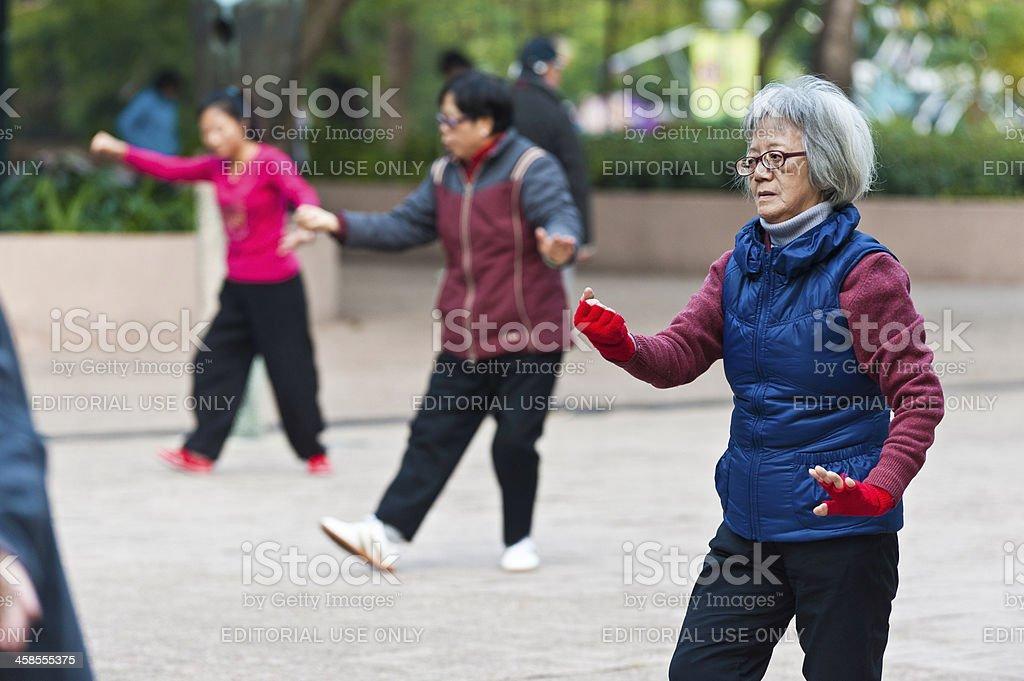 Senior Chinese woman practising Tai Chi in park Hong Kong royalty-free stock photo