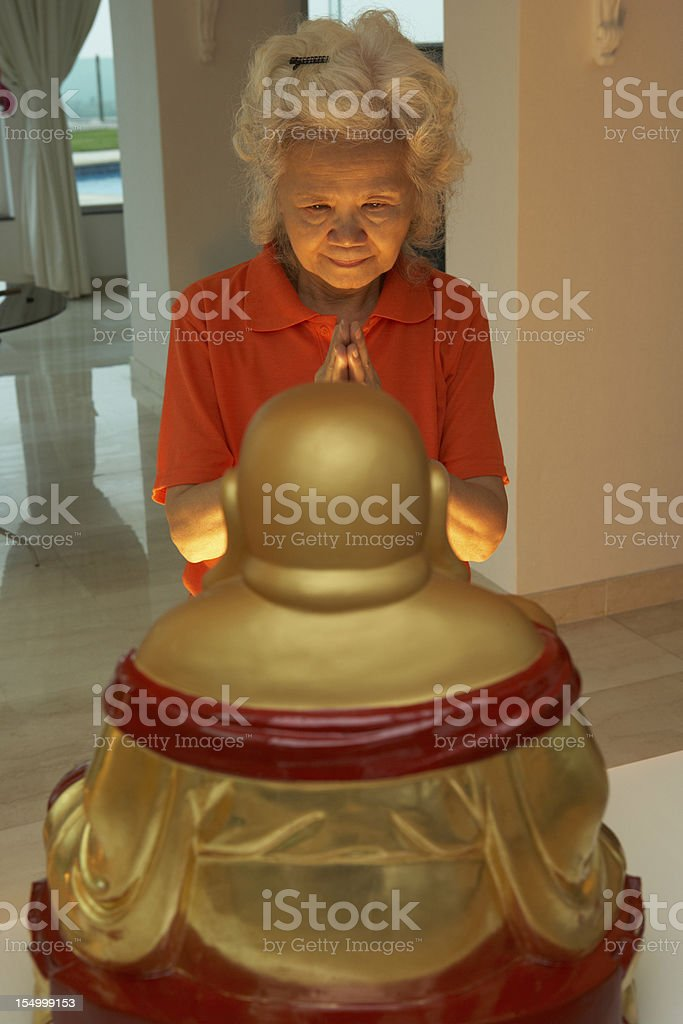 Senior Chinese Woman Praying To Statue Of Buddha At Home royalty-free stock photo