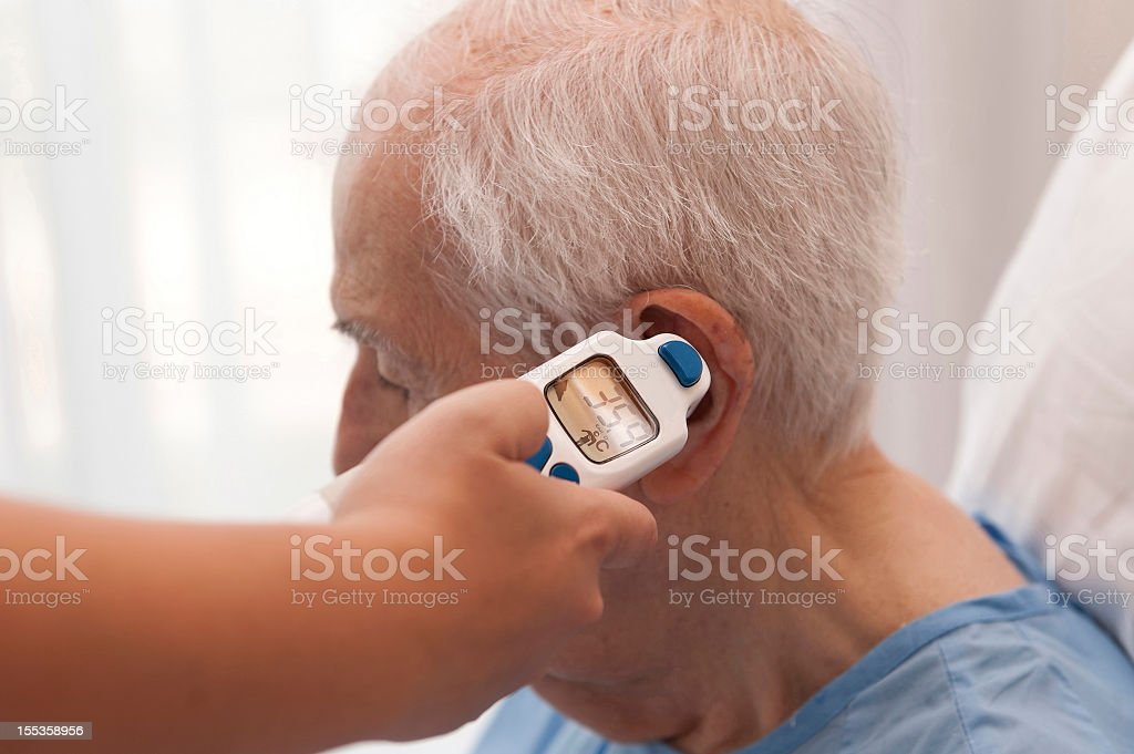 Senior citizen getting temperature taken from ear stock photo