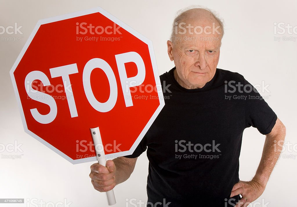 Senior citizen holds up 'STOP' sign stock photo