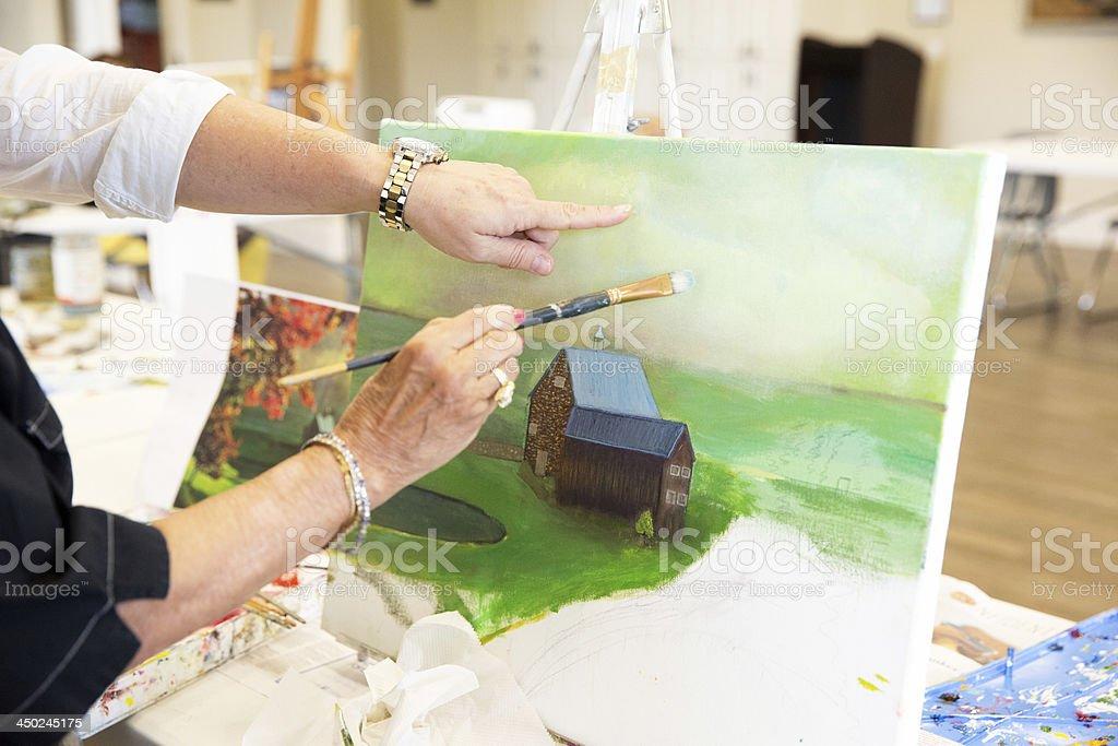 Senior citizen painting in art class stock photo
