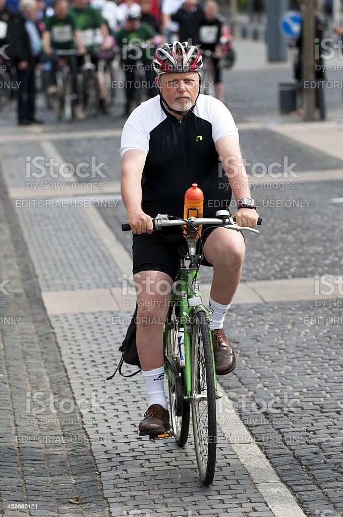 Senior citizen rides a bicycle royalty-free stock photo