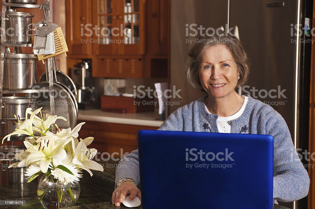 Senior citizen woman using a computer in the kitchen royalty-free stock photo