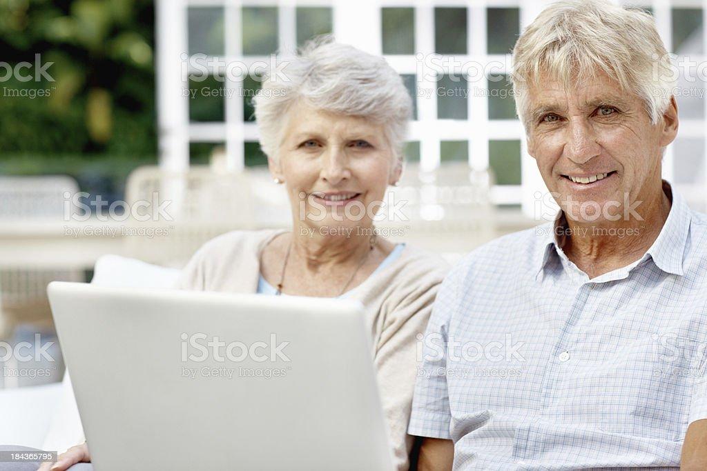 Senior citizens using laptop together royalty-free stock photo