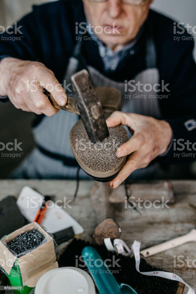 Senior cobbler repairing a shoe at the shop stock photo
