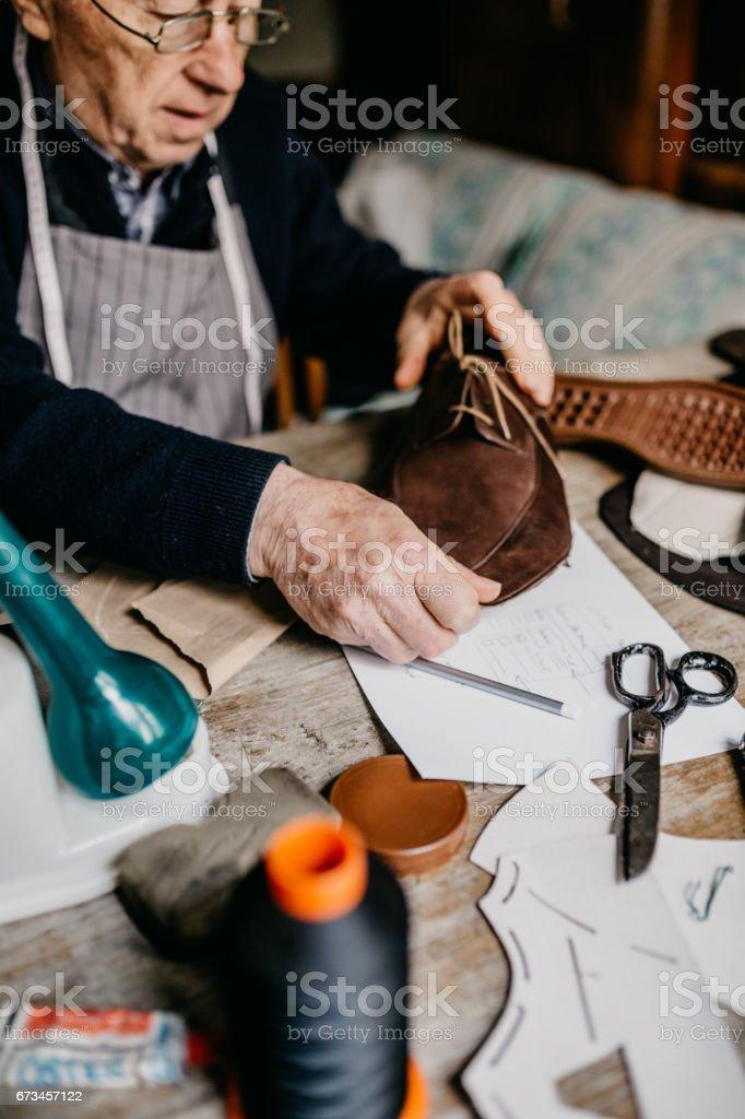 Senior cobbler working hard at the shop stock photo