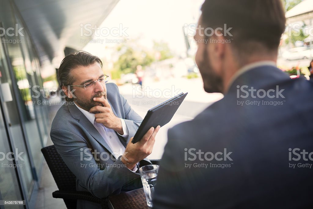 Senior colleague holding digital tablet and reviewing data. stock photo