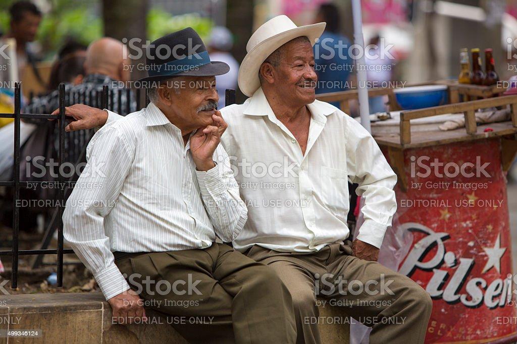 Senior colombian men sitting in a park, Medellin stock photo