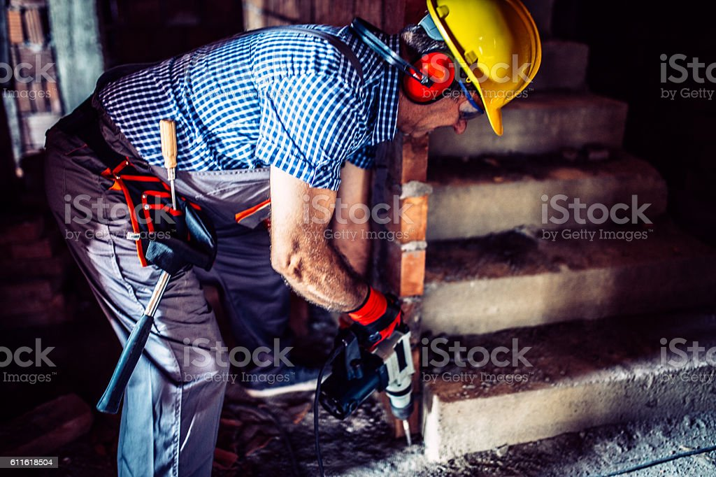 Senior construction worker drilling a hole stock photo