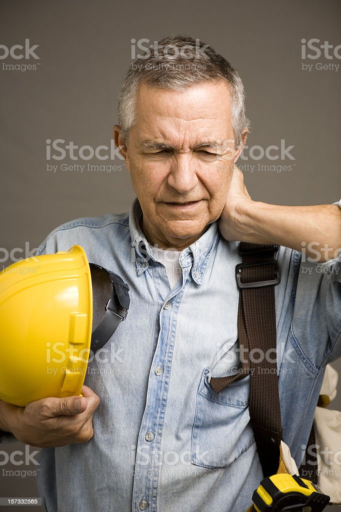Senior construction worker holding hard hat hand behind neck royalty-free stock photo