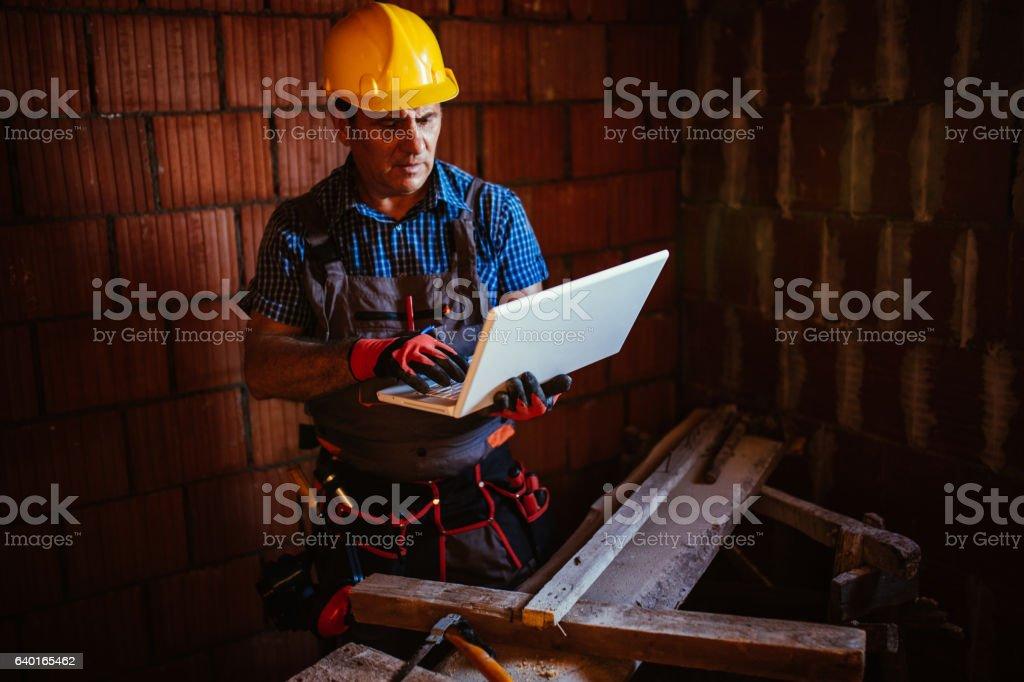 Senior Construction worker using laptop stock photo