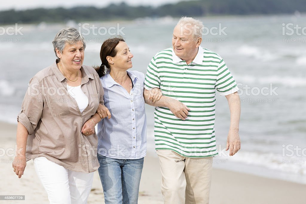 Senior couple and caregiver on the beach royalty-free stock photo
