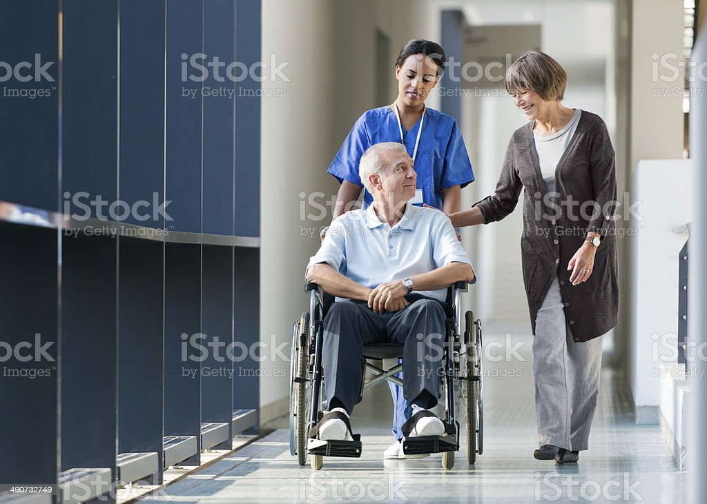 Senior Couple And Nurse Walking A Hospital Corridor stock photo