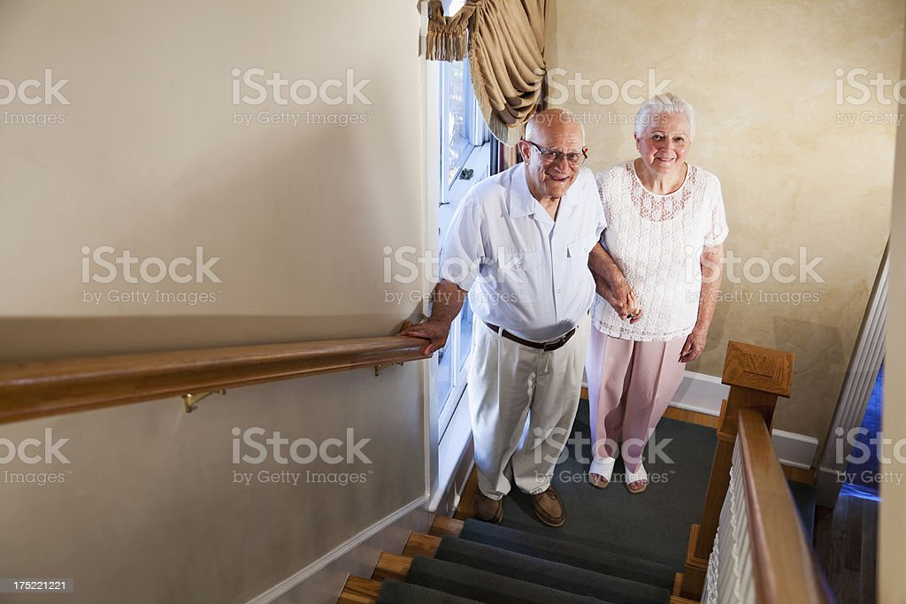 Senior couple at bottom of staircase looking up royalty-free stock photo