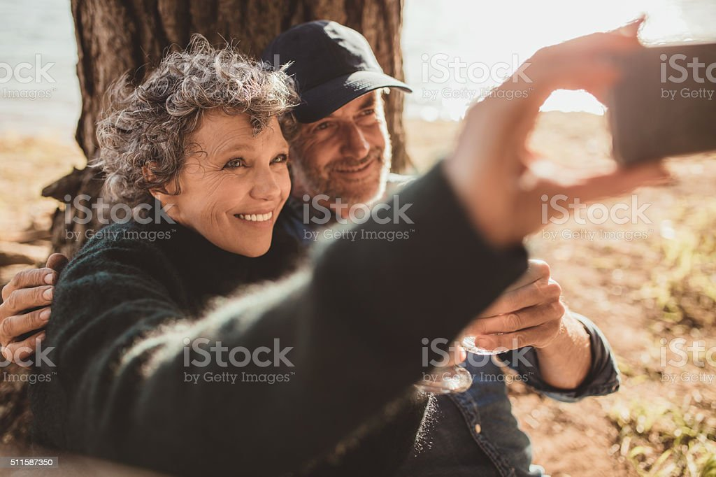 Senior couple at campsite taking selfie stock photo