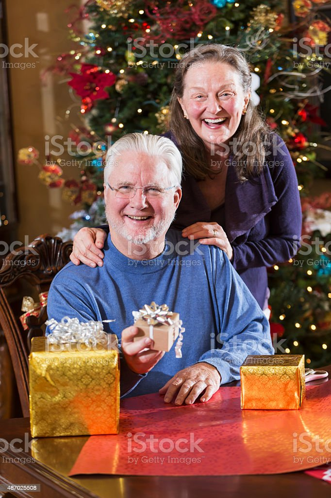 Senior couple at Christmas with gift boxes stock photo