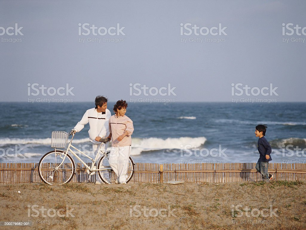 Senior couple at coast with grandson (5-7) stock photo