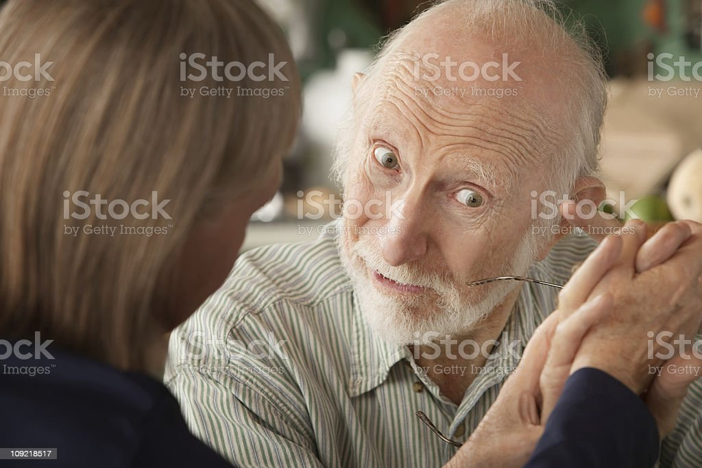 Senior couple at home holding hands focusing on man royalty-free stock photo