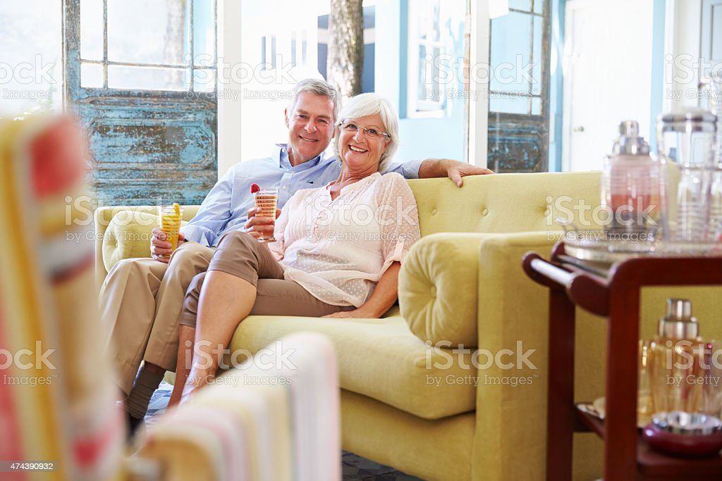 Senior Couple At Home Relaxing In Lounge With Cold Drinks stock photo