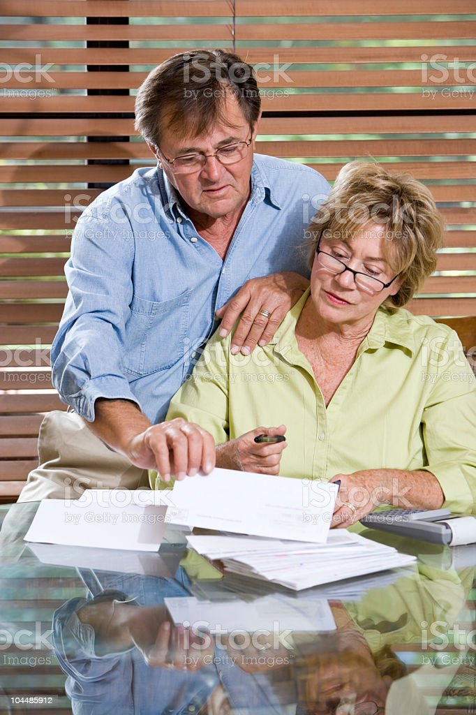 Senior couple at home reviewing finances, paying bills together royalty-free stock photo