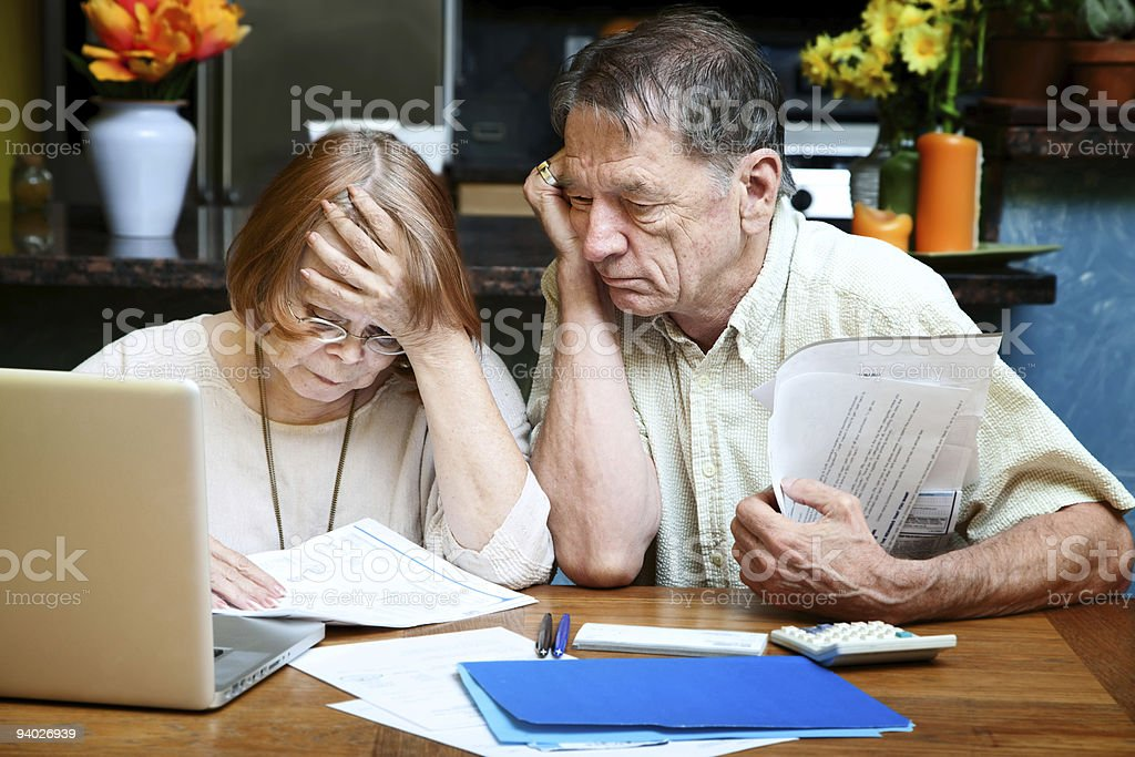 Senior couple at home with many bills stock photo