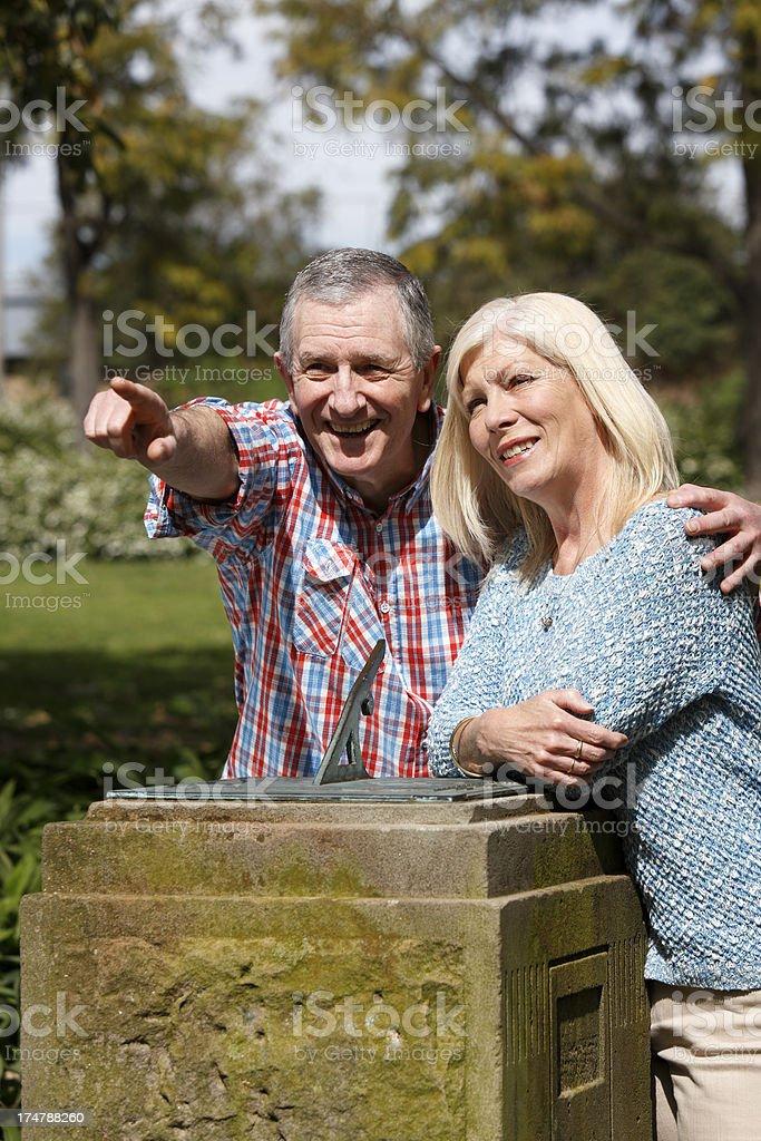 Senior couple at sundial in park royalty-free stock photo
