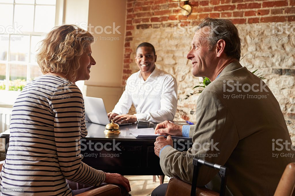 Senior couple at the check in desk stock photo