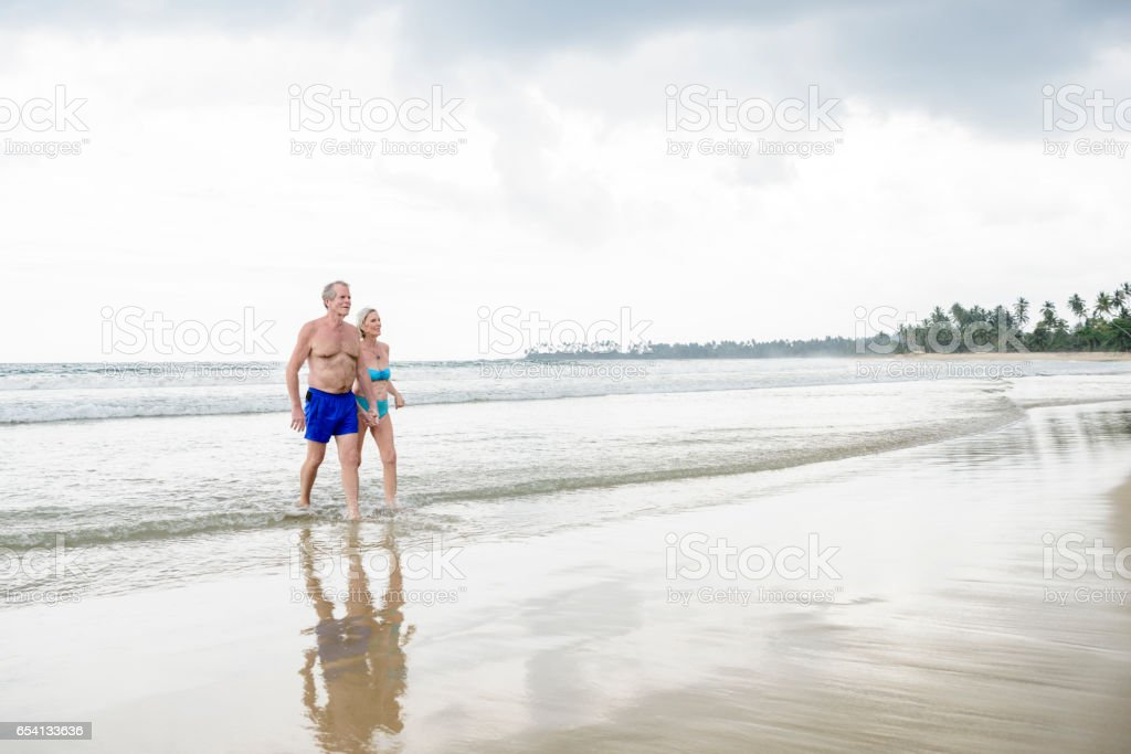 Senior couple at water's edge holding hands stock photo
