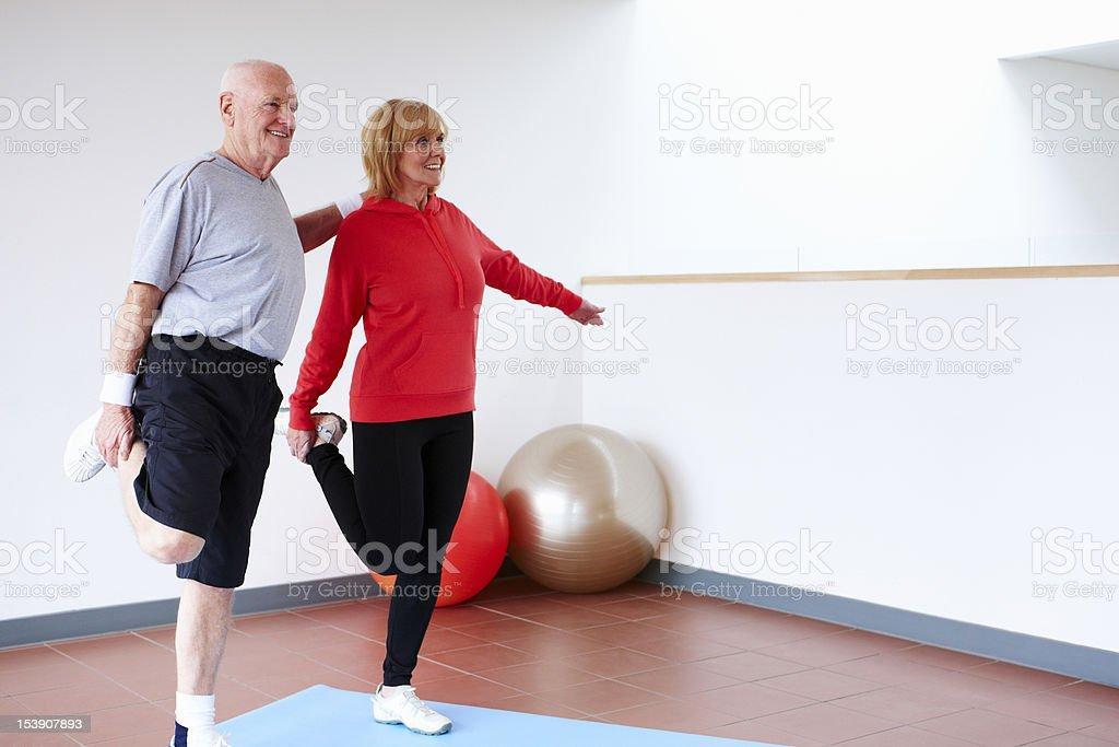 Senior Couple Balancing on One Leg royalty-free stock photo