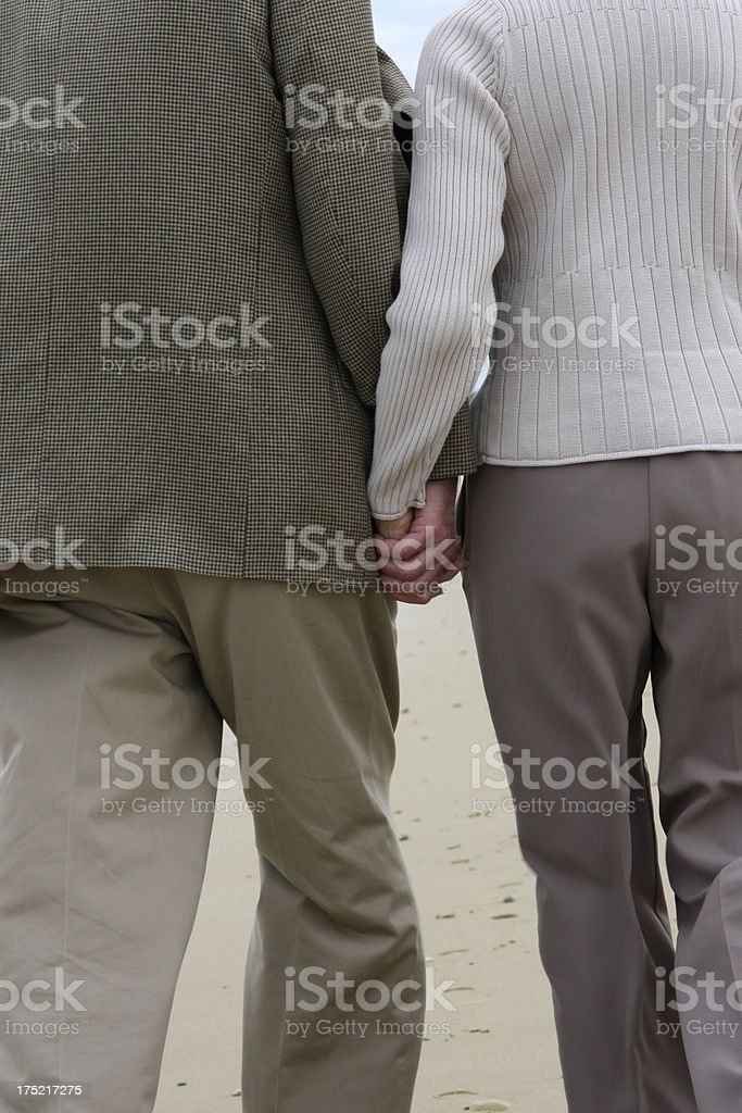 Senior couple beach walk holding hands - anonymous royalty-free stock photo
