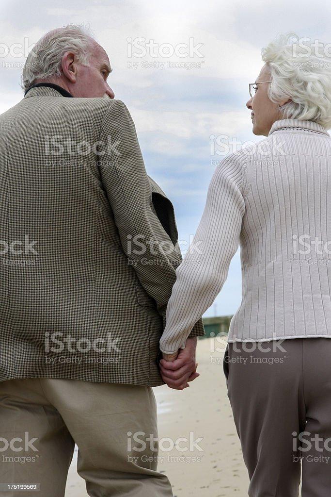 Senior couple beach walk holding hands royalty-free stock photo