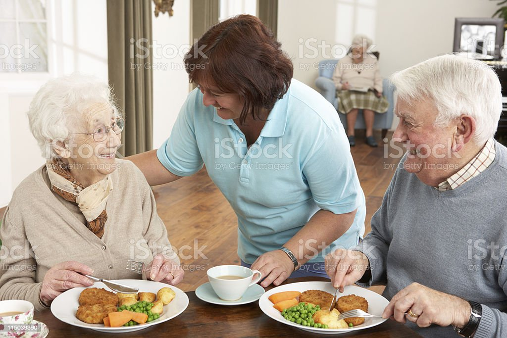 Senior Couple Being Served Meal By Carer stock photo