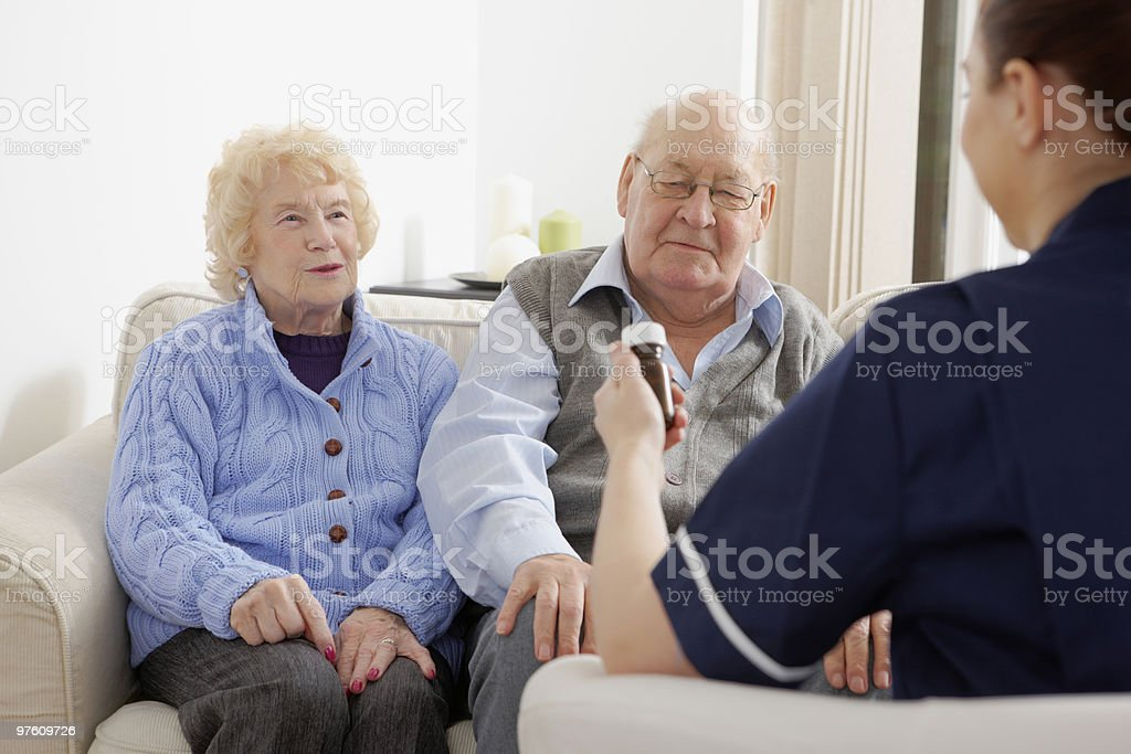 Senior couple being visited by a nurse at home royalty-free stock photo