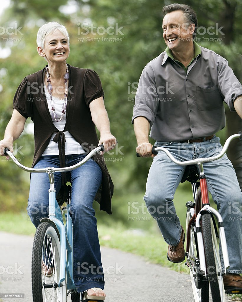 Senior Couple Biking Together in the Park royalty-free stock photo