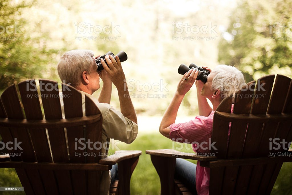 Senior Couple Birdwatching on a Wood Deck stock photo