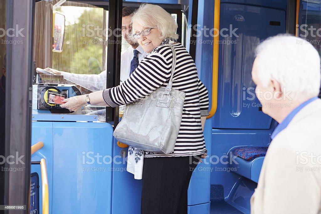 Senior Couple Boarding Bus And Using Pass stock photo