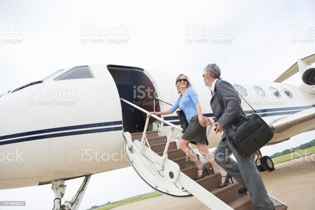 Senior couple boarding luxurious private jet stock photo