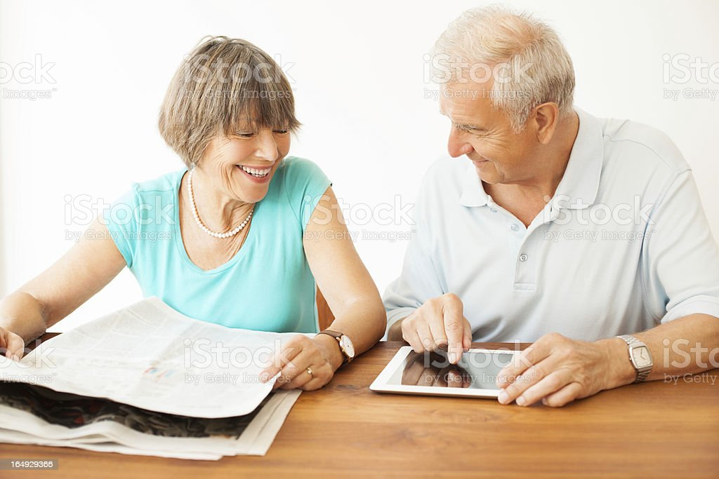 Senior couple both with newspaper and digital tablet stock photo