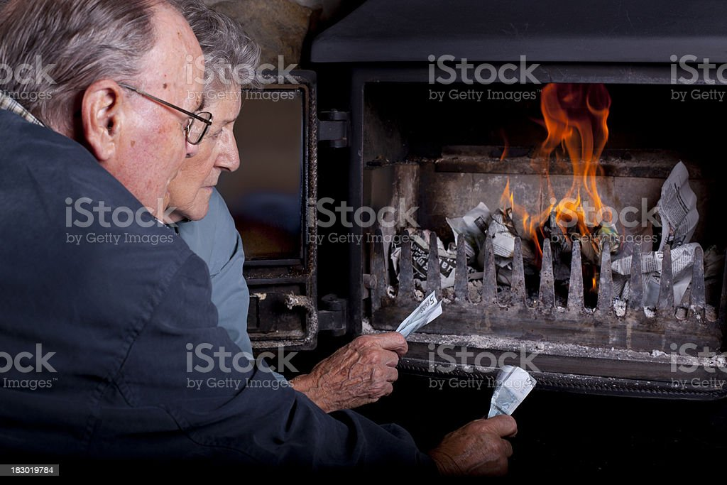 senior couple burning money for warmth stock photo