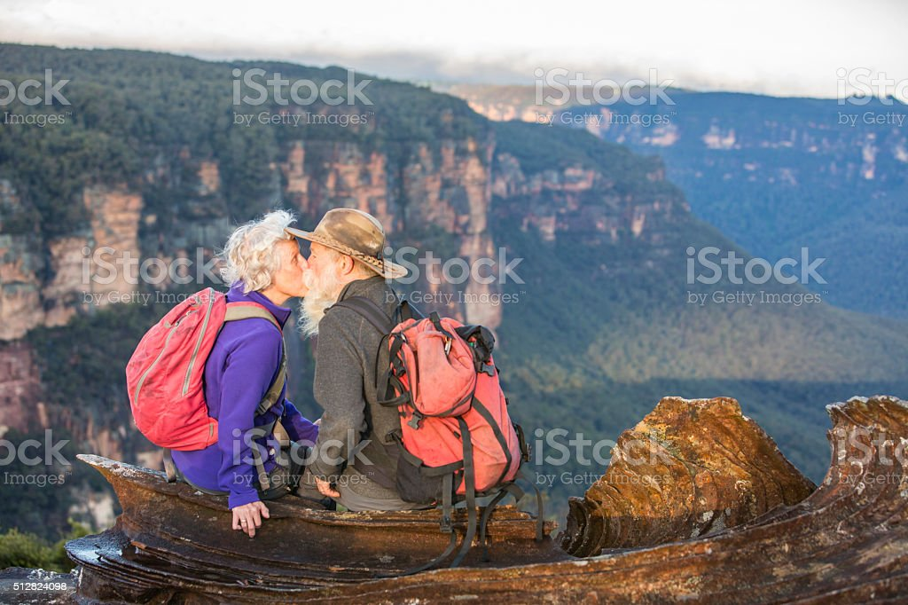 Senior Couple Bushwalkers Kissing With Spectacular Landscape Views stock photo