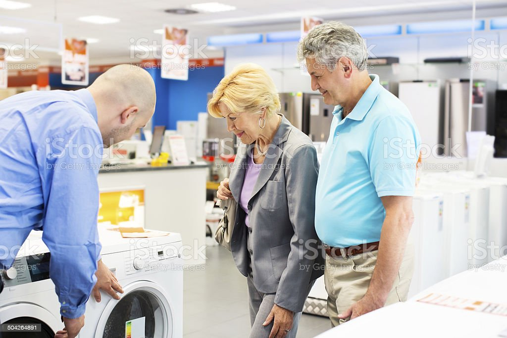 Senior couple buying a washing machine stock photo