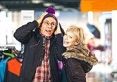 Senior couple buying clothes at shopping center