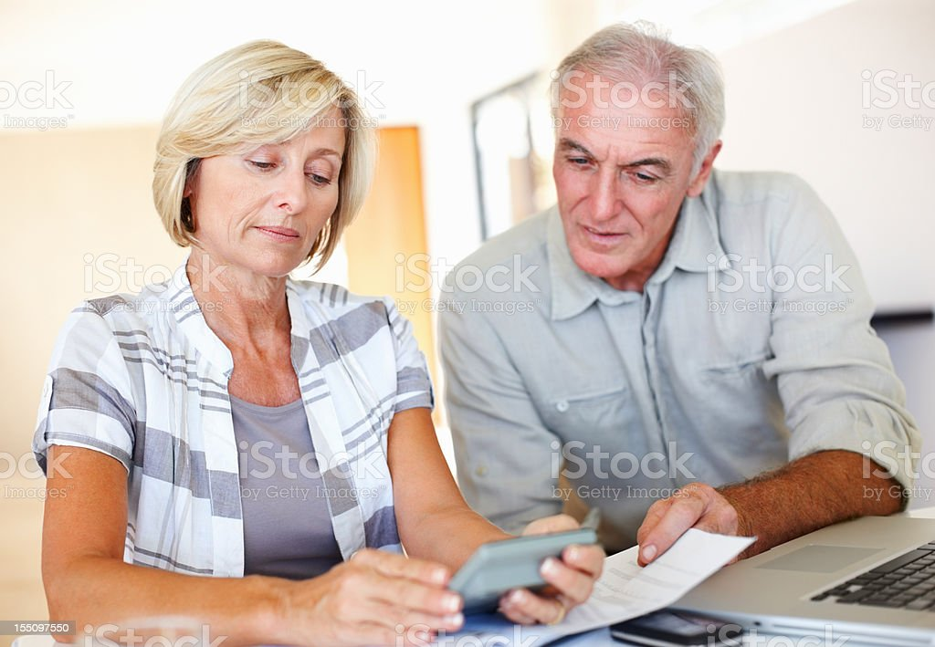 Serious elderly couple calculating their financial expenses using...